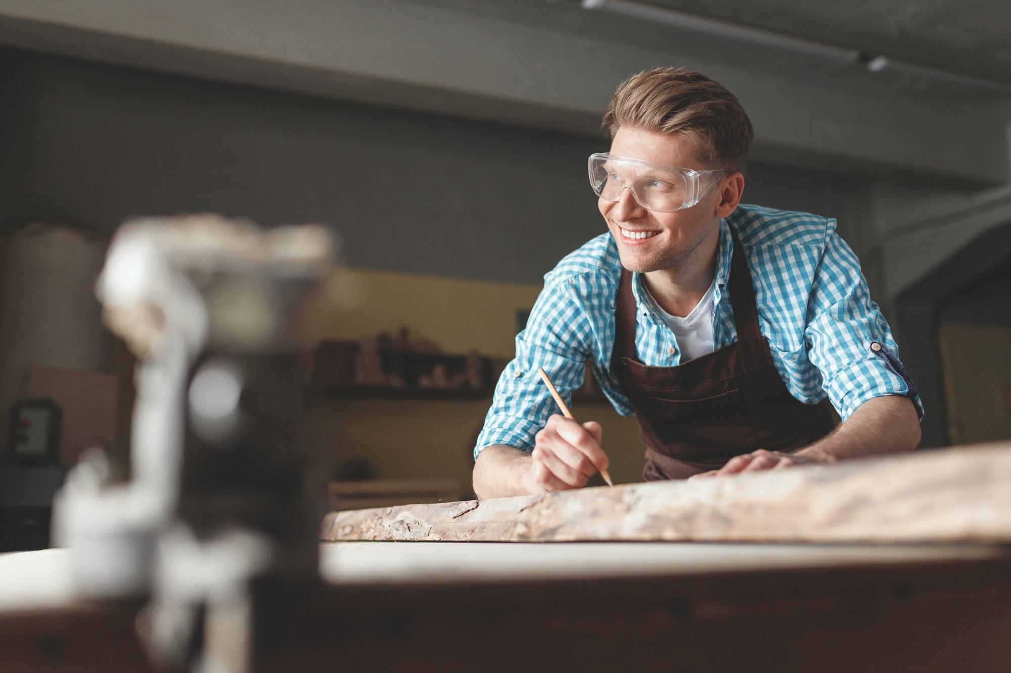 Young smiling carpenter at work